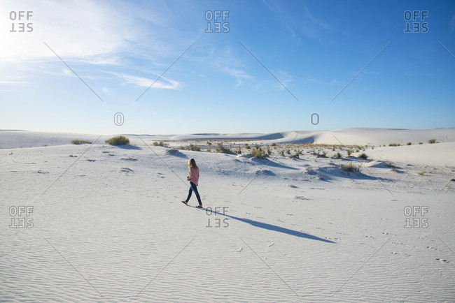 Rear view of woman walking along a sand dune in White Sands National Park near Alamogordo, New Mexico