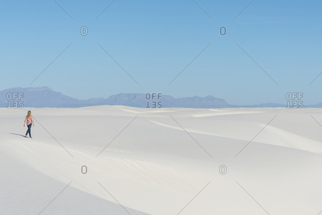 Blonde woman walking along a sand dune in White Sands National Park near Alamogordo, New Mexico