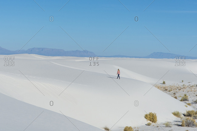Rear view of a blonde woman walking along a sand dune in White Sands National Park near Alamogordo, New Mexico