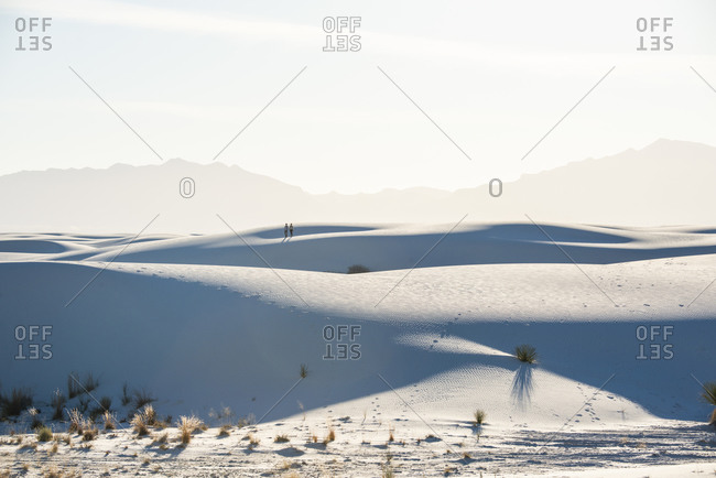 Couple walking along a sand dune in White Sands National Park near Alamogordo, New Mexico