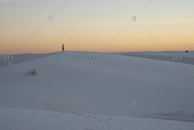 Man standing on a dune in White Sands National Park near Alamogordo, New Mexico at sunset