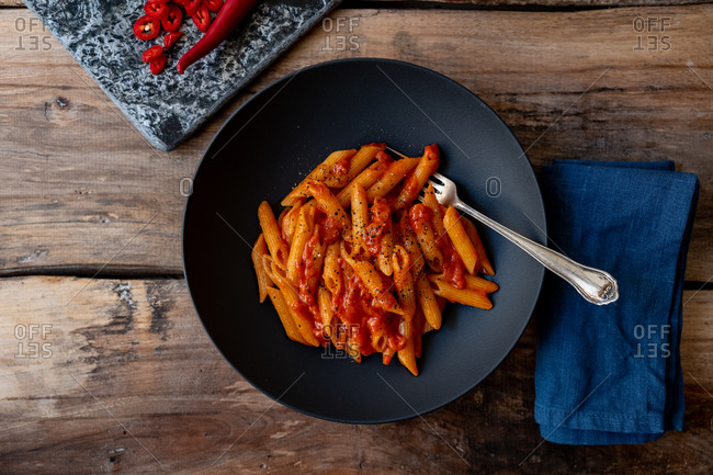 Overhead view of penne pasta dish with peppers on wooden surface