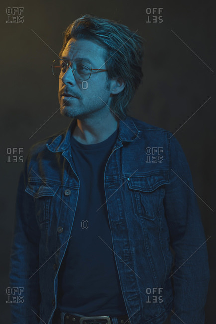 Profile view of a man wearing a denim jacket under blue light