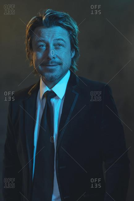 Man dressed in a black tuxedo under blue light