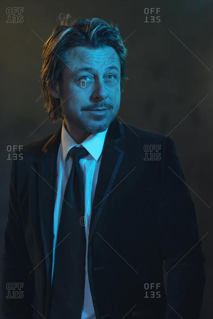 Portrait of a man dressed in a black tuxedo under blue light