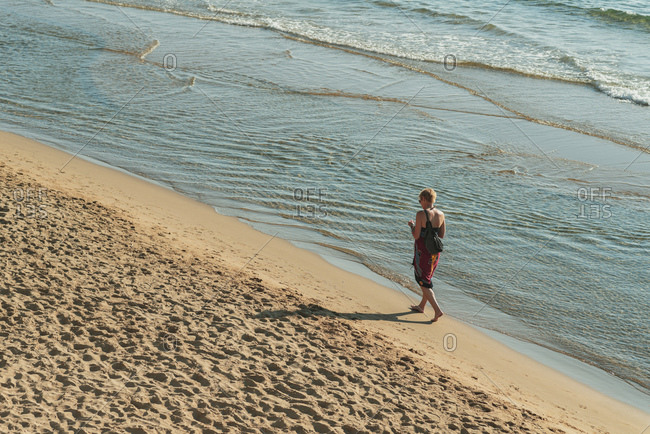 Elevated view of woman walking barefoot on sandy beach