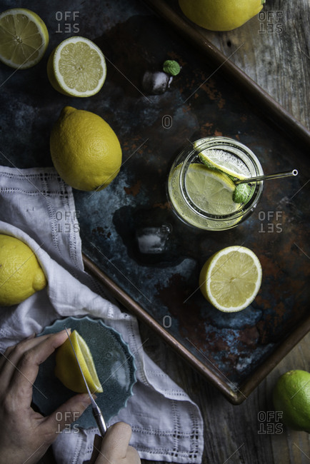 Overhead view of person preparing lemon infused water on a rustic tray