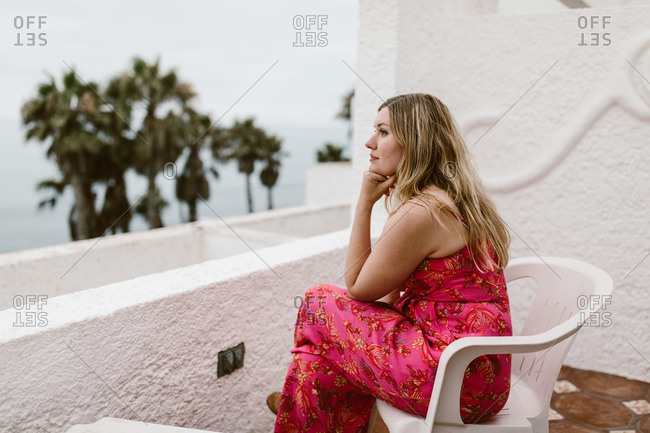 Woman sitting on her balcony overlooking the beach in Mexico