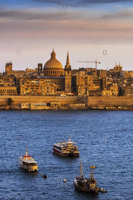 Malta- Valletta- City skyline at sunset- boats in Marsamxett Harbor in foreground