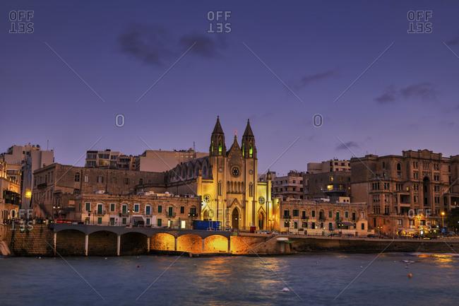 Malta- St. Julian- Town skyline at night with Carmelite Church at Balluta Bay
