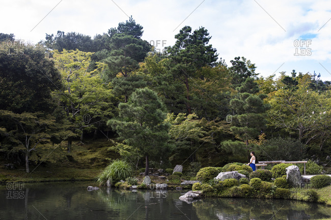 Japan- Kyoto Prefecture- Kyoto- Young woman meditating in front of Sogen Pond
