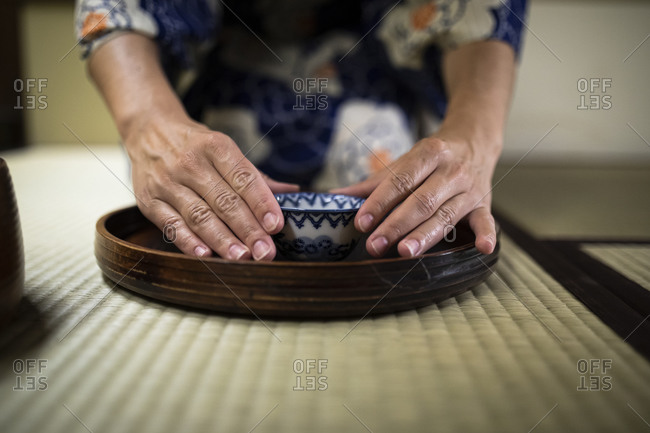 Japan- Hands of woman holding tea cup during tea ceremony