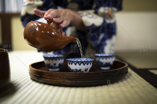 Japan- Hands of woman pouring tea into cups during tea ceremony