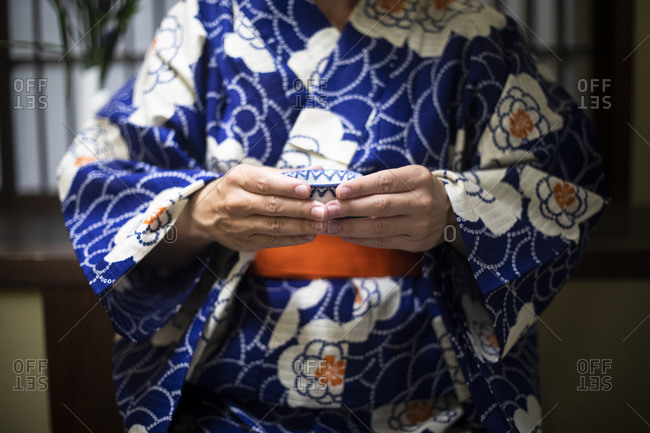Japan- Mid section of woman wearing traditional kimono holding tea cup
