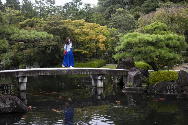 Japan- Himeji- Woman on footbridge in Adelaide Himeji Gardens