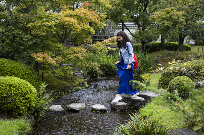 Japan- Kyoto- Woman on stepping stones in pond