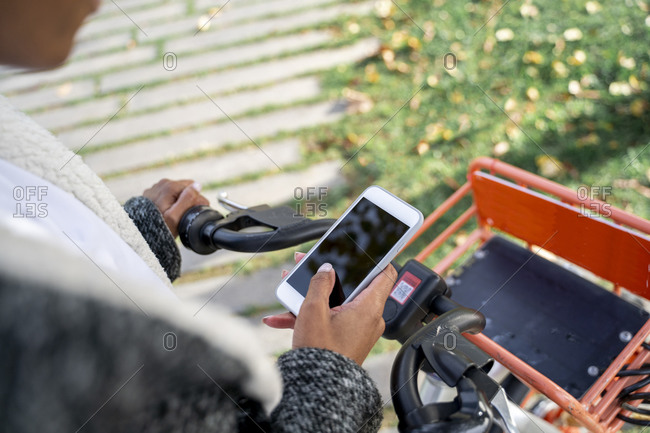 Businesswoman using bicycle-sharing system- using smartphone