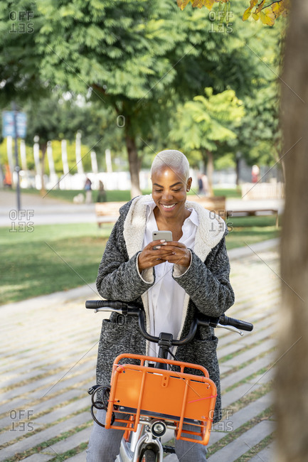 Businesswoman commuting in the city with her bicycle- using smartphone