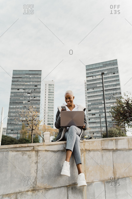 Casual businesswoman sitting in the city- using laptop