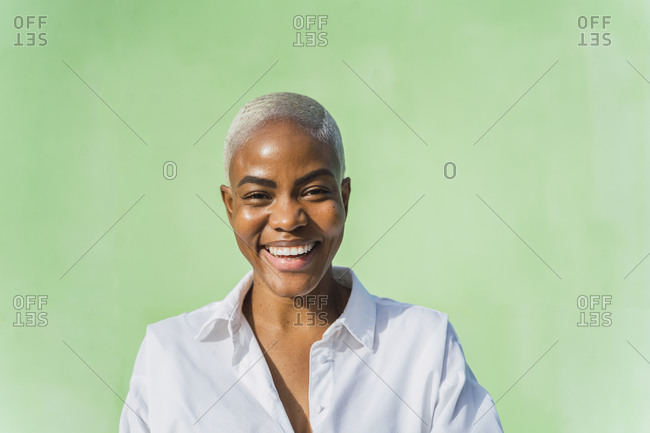 Portrait of laughing woman in front of green wall