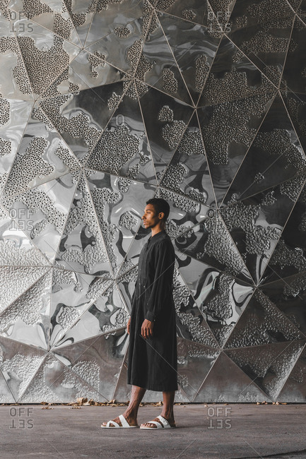 Young man wearing black kaftan standing at structured wall