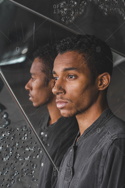 Portrait of young man at mirrored wall