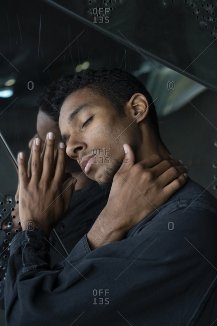 Portrait of young man with closed eyes at mirrored wall