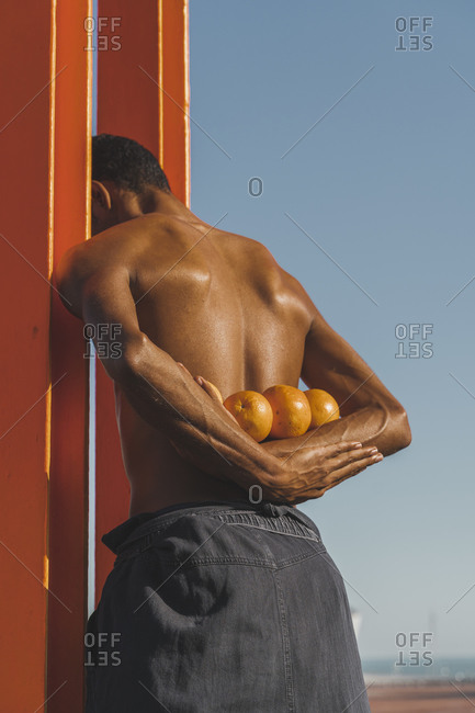Bare-chested young man holding oranges outdoors