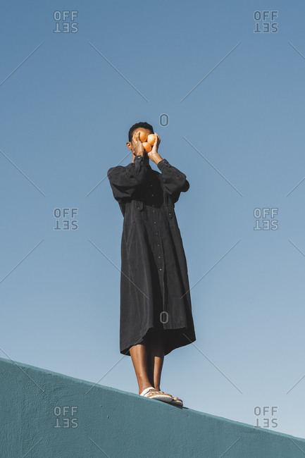Young man wearing black kaftan standing on blue wall holding oranges in front of his face