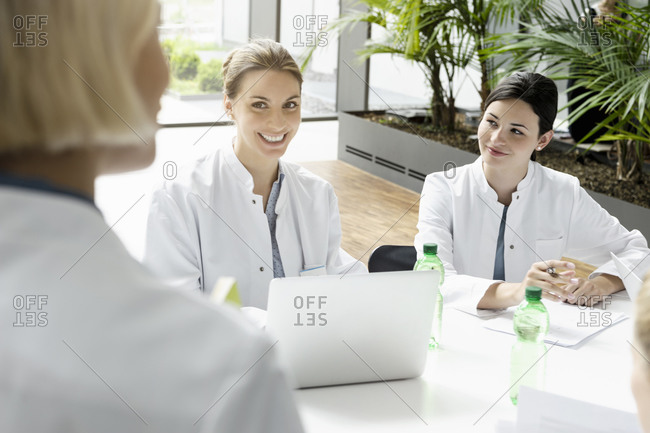 Portrait of smiling female doctor with laptop in a meeting