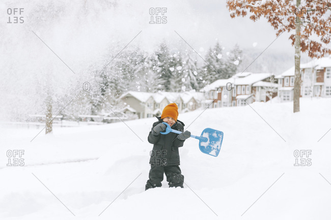 Laughing little boy shoveling snow- Vancouver- Canada