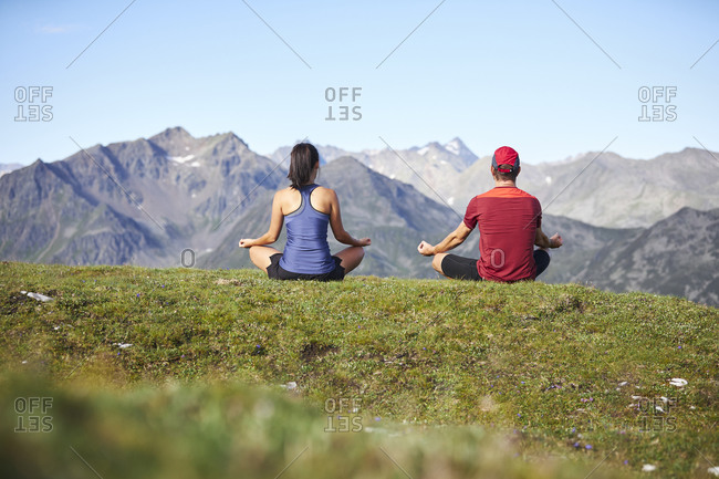 Man and woman meditating in the mountains- rear view