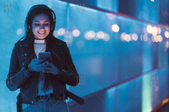Portrait of smiling teenage girl with headphones standing in front of blue glass pane looking at smartphone
