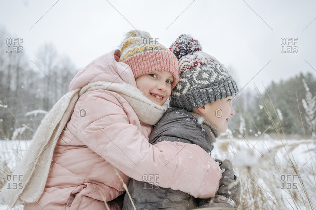 Boy giving his little sister a piggyback ride in winter forest