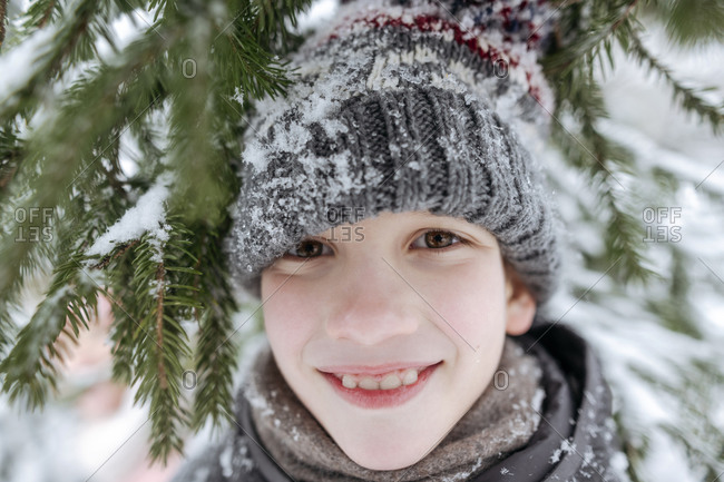 Portrait of smiling boy having fun in winter forest