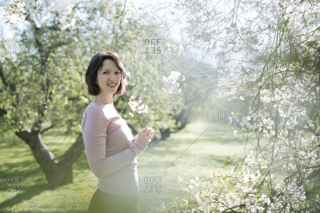 Portrait of smiling woman with twig of blossoming cherry tree at sunlight