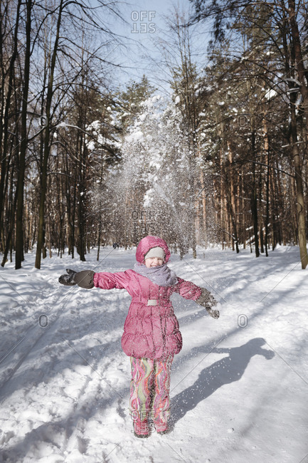 Little girl throwing snow in winter forest