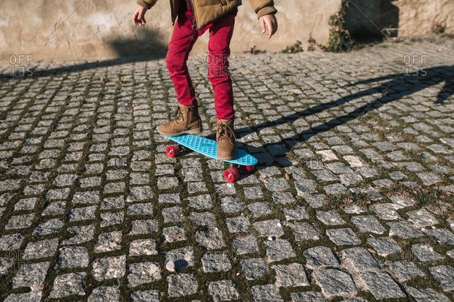 Low section of boy riding skateboard