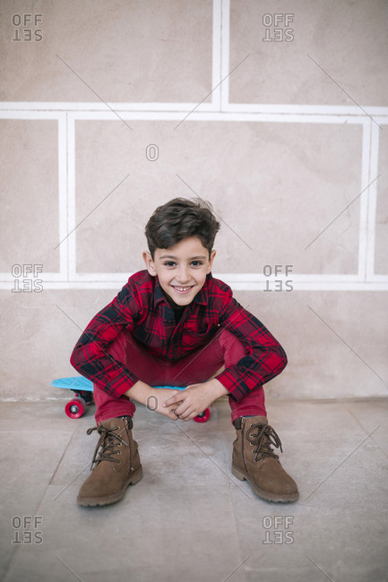Portrait of smiling boy sitting on skateboard at a wall