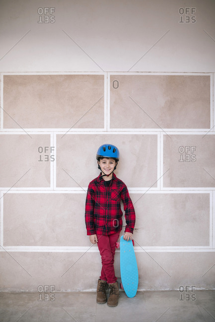 Portrait of smiling boy wearing helmet holding skateboard at a wall