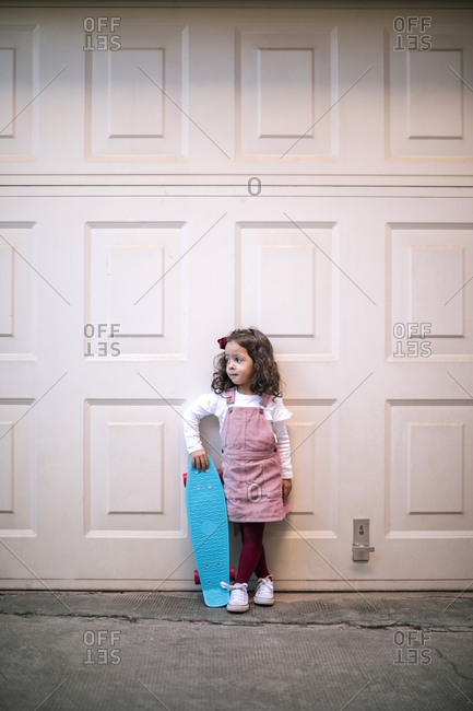 Girl holding skateboard at a garage