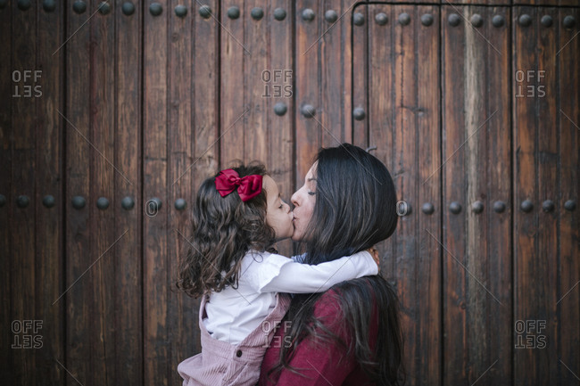 Mother holding and kissing little daughter outdoors