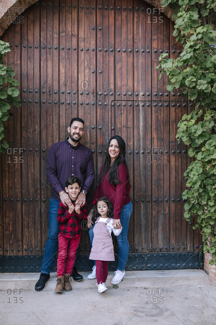 Portrait of smiling family with two children standing at wooden gate