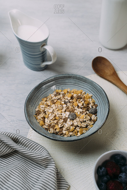 Bowl of granola with jug of yogurt in background