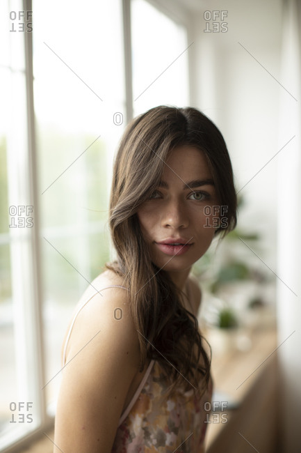 Portrait of beautiful young woman at the window at home