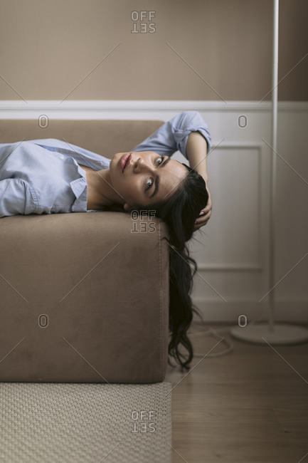 Portrait of beautiful young woman lying on couch at home