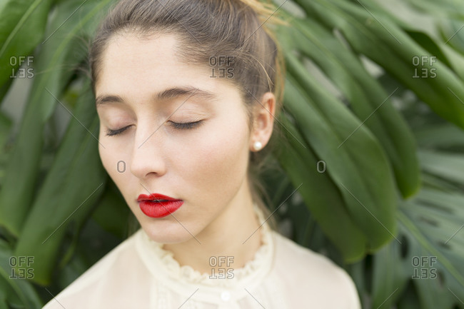 Portrait of young woman with red lips and eyes closed relaxing