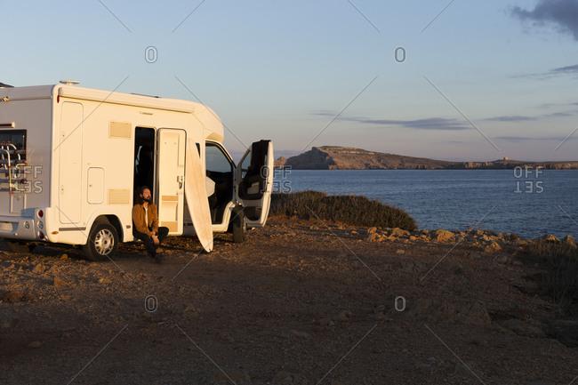 Man sitting at opened car door of camper enjoying sunlight- Es Mercadal- Menorca- Spain