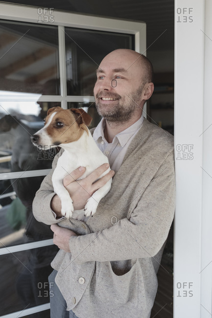 Portrait of relaxed man with dog on his arms standing at open terrace door of his house