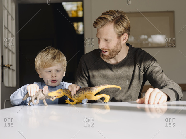 Father and son playing with dinosaur figures at home